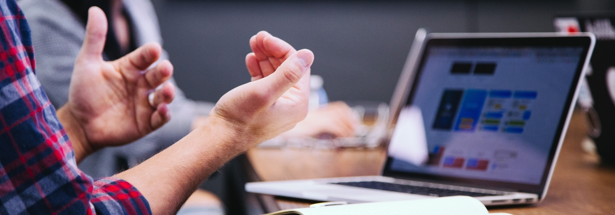 A male gesturing while in a meeting