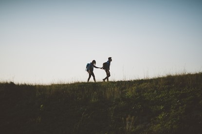 A couple showing resilience on a walk up a hill